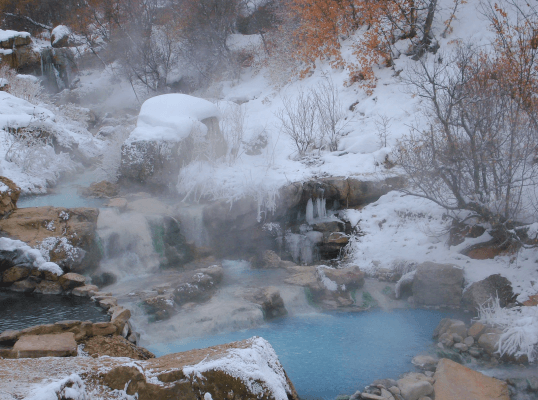 Crystal hot springs in winter. Snow and ice surround milky blue pools.